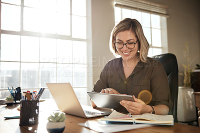 Buy stock photo Cropped shot of a businesswoman using a digital tablet while sitting at her desk