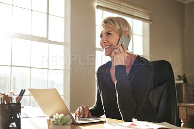 Buy stock photo Shot of a businesswoman talking on her cellphone while using her laptop