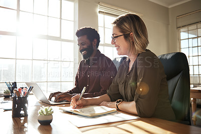 Buy stock photo Cropped shot of two businesspeople working together using a laptop in an office