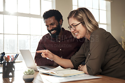 Buy stock photo Shot of two colleagues discussing something on a laptop while sitting together in an office