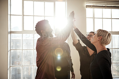 Buy stock photo Cropped shot of a group of creative workers joining in for a high five