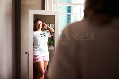 Buy stock photo Shot of a young woman looking at herself in the mirror
