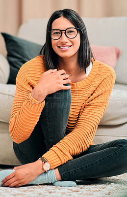 Buy stock photo Shot of a young woman relaxing on the floor in the living room at home