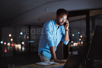 Buy stock photo Cropped shot of a handsome young businessman making a phonecall while working late at night in his office