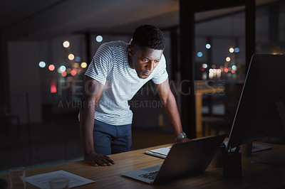 Buy stock photo Cropped shot of a handsome young businessman working on his laptop late at night in the office
