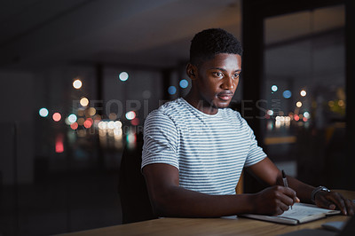 Buy stock photo Cropped shot of a handsome young businessman making notes while working late at night in his office