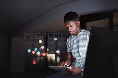 Buy stock photo Cropped shot of a handsome young businessman working on his tablet late at night in the office