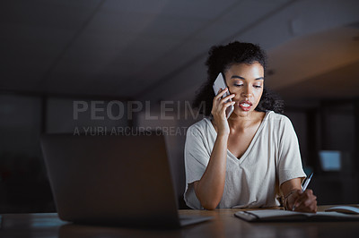 Buy stock photo Cropped shot of an attractive young businesswoman making a phonecall and writing notes while working late at night in her office