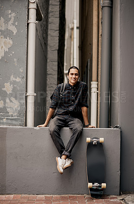 Buy stock photo Full length portrait of a young handsome man smiling and sitting on a wall outside during the day