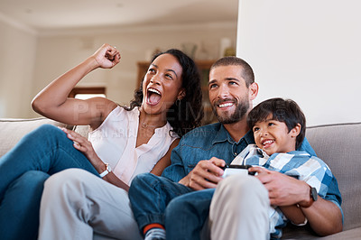 Buy stock photo Shot of a man playing video games while relaxing at home with his wife and son