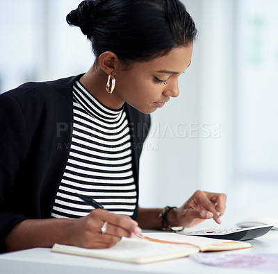 Buy stock photo Shot of an attractive young businesswoman working out her finances with a calculator and notepad in her office