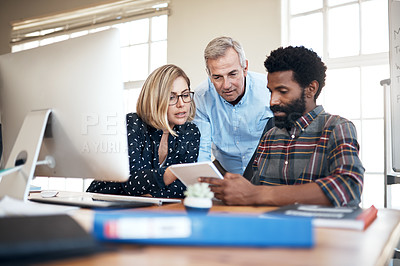 Buy stock photo Cropped shot of a diverse group of businesspeople sitting together and reading a notebook in the office