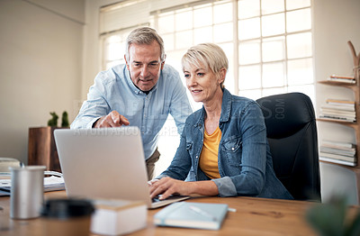 Buy stock photo Cropped shot of two mature businesspeople sitting in the office together and using a laptop
