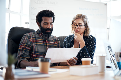 Buy stock photo Cropped shot of two creative young businesspeople going over paperwork together inside an office