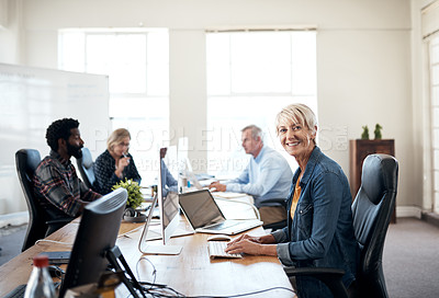 Buy stock photo Portrait of a creative mature businesswoman working inside a modern office with her colleagues in the background