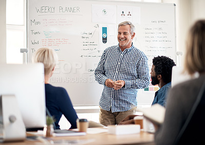 Buy stock photo Cropped shot of a mature businessman presenting and pitching ideas to his colleagues inside an office