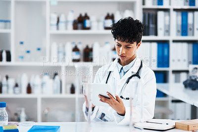 Buy stock photo Shot of a young scientist using a digital tablet in a lab