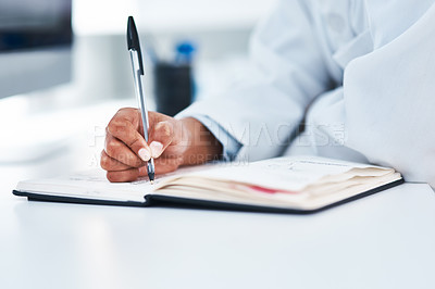 Buy stock photo Closeup shot of an unrecognisable scientist writing notes in a lab