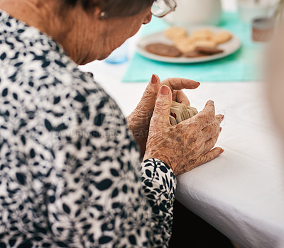 Buy stock photo Cropped shot of a senior woman sitting and shuffling a deck of cards before a game of bridge outdoors