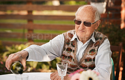 Buy stock photo Cropped shot of a happy senior man sitting and pouring wine into glasses during a birthday party outdoors