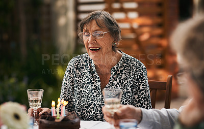 Buy stock photo Cropped shot of a happy senior woman sitting with her friends and blowing out candles during her birthday party