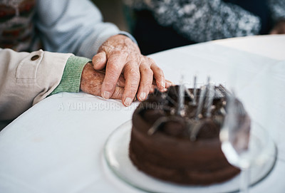 Buy stock photo Cropped shot of an unrecognizable senior couple sitting together and holding hands during a birthday party outdoors