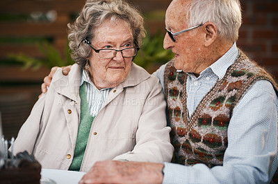 Buy stock photo Cropped shot of a happy senior couple sitting together during a birthday party outdoors
