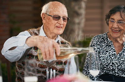 Buy stock photo Cropped shot of a happy senior man sitting and pouring champagne into glasses during a birthday party outdoors
