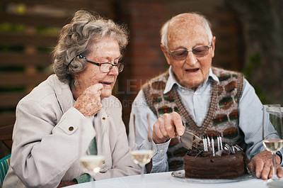 Buy stock photo Cropped shot of a happy senior couple sitting together and cutting chocolate cake during a birthday party outdoors