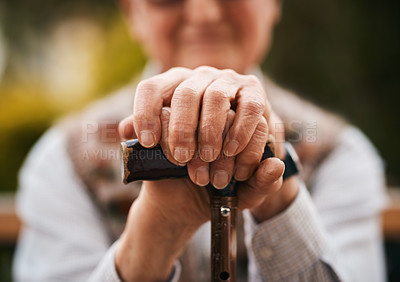 Buy stock photo Cropped shot of an unrecognizable senior man sitting outdoors alone and holding his walking stick