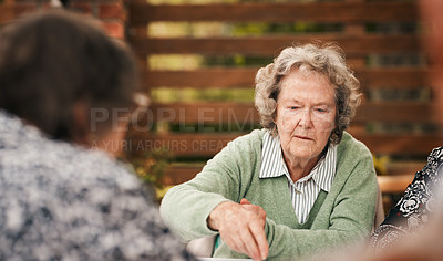Buy stock photo Cropped shot of a senior woman sitting and looking contemplative during a game of mahjong with her friends