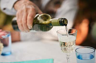 Buy stock photo Cropped shot of an unrecognizable senior man sitting and pouring wine into glasses for a toast during a birthday party