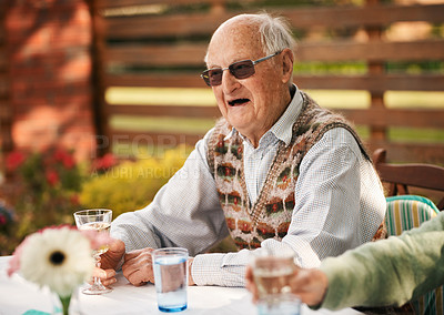 Buy stock photo Cropped shot of a happy senior man sitting and enjoying a glass of wine during a birthday party outdoors