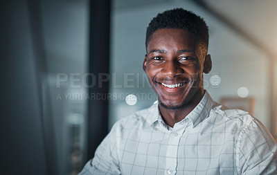 Buy stock photo Cropped shot of a handsome young businessman sitting alone in his office during a late shift