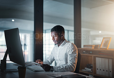 Buy stock photo Cropped shot of a handsome young businessman sitting alone and working on his computer in the office at night