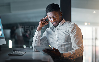 Buy stock photo Cropped shot of a handsome young businessman sitting alone in his office and feeling stressed during a late night
