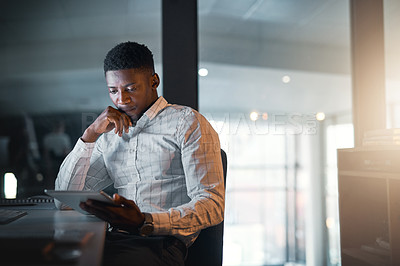 Buy stock photo Cropped shot of a handsome young businessman sitting in his office and looking contemplative while using a tablet at night