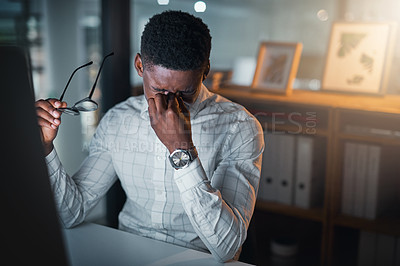 Buy stock photo Cropped shot of a handsome young businessman sitting and suffering from a headache during a late shift in the office