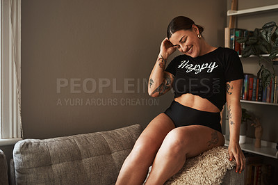 Buy stock photo Cropped shot of an attractive young woman smiling while sitting on her couch at home