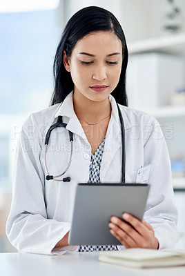 Buy stock photo Shot of a young doctor using a digital tablet while working in a clinic