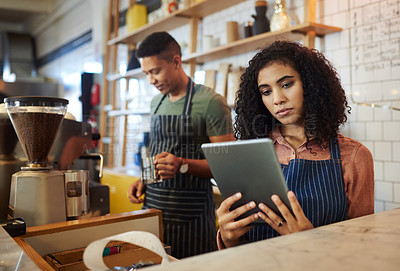 Buy stock photo Shot of a young woman using a digital tablet while working in a cafe with her colleague in the background