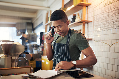 Buy stock photo Shot of a young man talking on a phone while going through notes on a clipboard in a cafe