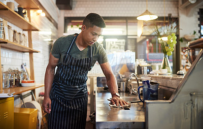 Buy stock photo Shot of a young man cleaning a countertop in a cafe