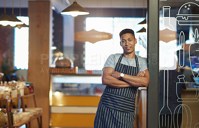 Buy stock photo Portrait of a young man standing in the doorway of a cafe