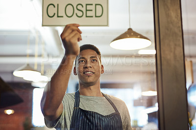 Buy stock photo Shot of a young man hanging up a