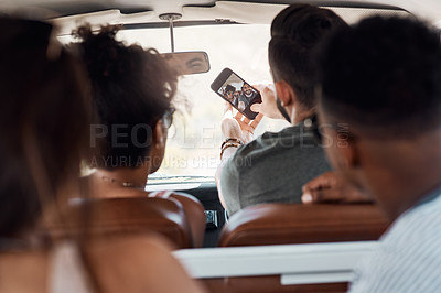 Buy stock photo Shot of a group of happy young friends taking selfies during a road trip