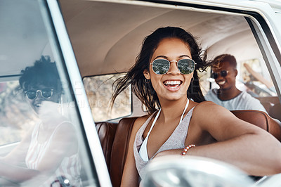 Buy stock photo Shot of a happy young woman enjoying a road trip with her friends