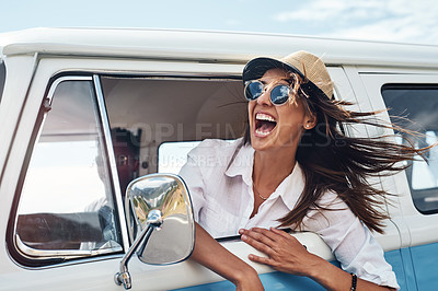 Buy stock photo Shot of a happy young woman enjoying a road trip