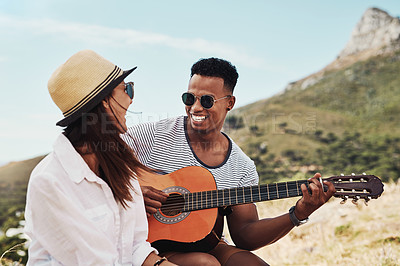 Buy stock photo Shot of a young man playing the guitar while sitting outdoors with his girlfriend