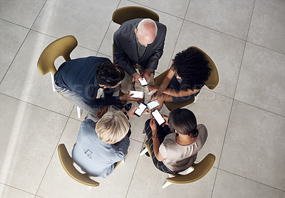 Buy stock photo High angle shot of a group of unrecognizable businesspeople using smartphones while sitting together in a modern office